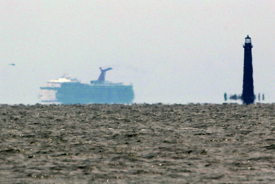 The cruise ship Carnival Triumph is visible several miles beyond the Sand Island Light House near Dauphin Island, Ala., Thursday, Feb. 14, 2013. The ship with over 1,000 passengers aboard has been idled for nearly a week in the Gulf of Mexico following an engine room fire, and is being towed to port in Mobile, Ala. (AP Photo/Dave Martin) Photo: Dave Martin, Associated Press / AP