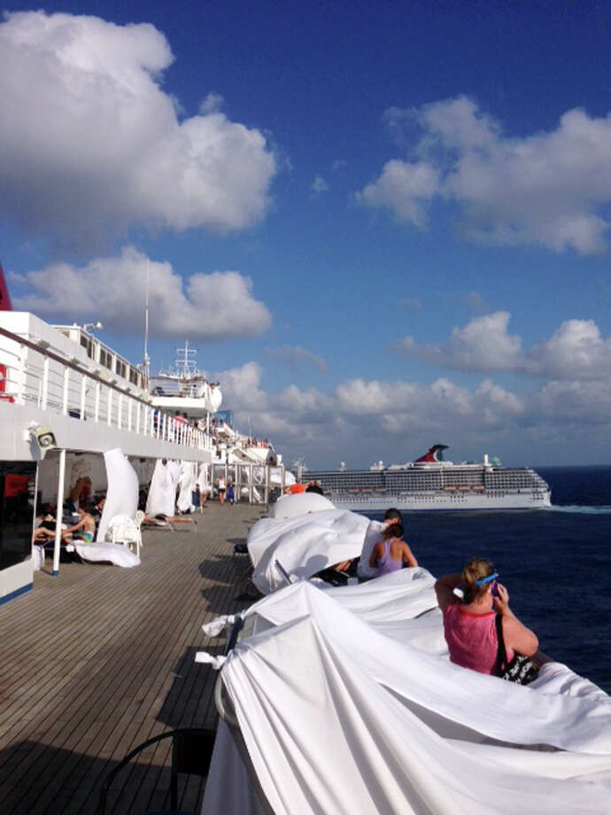 This Sunday, Feb. 10, 2013 photo, provided by Kalin Hill, of Houston, shows passengers with makeshift tents on the the deck of the Carnival Triumph cruise ship at sea in the Gulf of Mexico. The ship nearing Mobile Bay is without engine power and is being towed by tugboats. (AP Photo/Kalin Hill) Photo: Kalin Hill, Associated Press / Kalin Hill