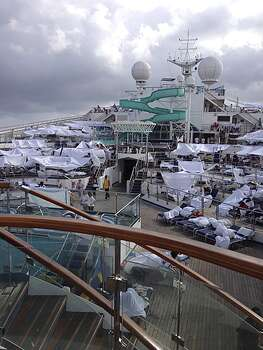 In this Sunday, Feb. 10, 2013 photo, provided by Kalin Hill of Houston, passengers with makeshift tents are seen on the the deck of the Carnival Triumph cruise ship at sea in the Gulf of Mexico. The ship nearing Mobile Bay is without engine power and is being towed by tugboats. (AP Photo/Kalin Hill) Photo: Kalin Hill, Associated Press / Kalin Hill