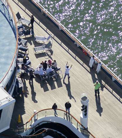 Passengers congregate on an upper deck of the disabled Carnival Lines cruise ship Triumph as it is towed to harbor off Mobile Bay, Ala., Thursday, Feb. 14, 2013. The ship with more than 4,200 passengers and crew members has been idled for nearly a week in the Gulf of Mexico following an engine room fire. (AP Photo/Gerald Herbert) Photo: Gerald Herbert, Associated Press / AP