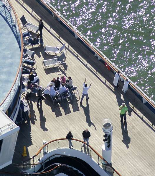 Passengers congregate on an upper deck of the disabled Carnival Lines cruise ship Triumph as it is t