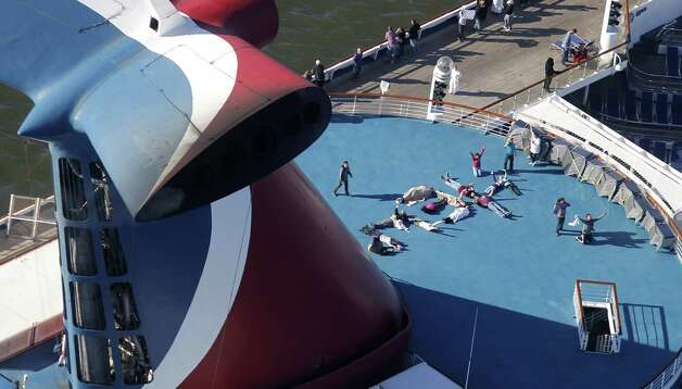 "Passengers spell out the word ""HELP"" aboard the disabled Carnival Lines cruise ship Triumph as it is towed to harbor off Mobile Bay, Ala., Thursday, Feb. 14, 2013. The ship with more than 4,200 passengers and crew members has been idled for nearly a week in the Gulf of Mexico following an engine room fire. (AP Photo/Gerald Herbert) Photo: Gerald Herbert, Associated Press / AP"