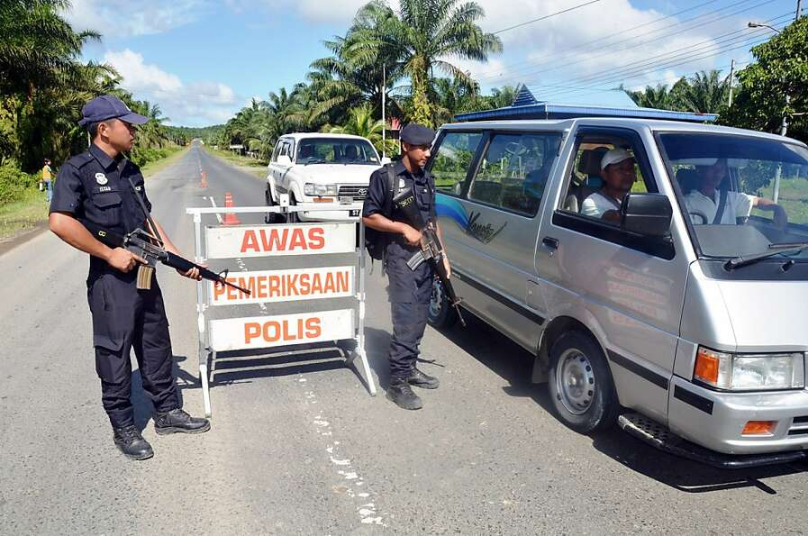 Malaysian police man a checkpoint in Sabah state, where officers surrounded a group of armed men.