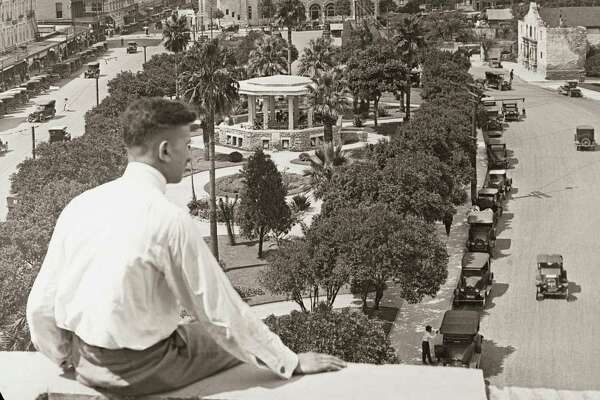"""In this image from the 1920s, readers of """"Downtown San Antonio"""" can look over the shoulder of this unknown man at Alamo Plaza."""