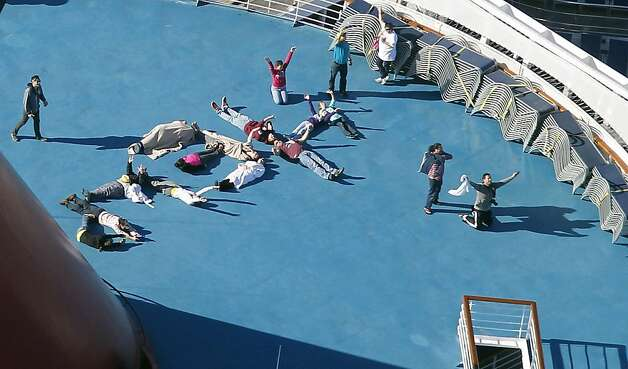 "Passengers spell out the word ""HELP"" aboard the disabled Carnival Lines cruise ship Triumph as it is towed to harbor off Mobile Bay, Ala., Thursday, Feb. 14, 2013. The ship with more than 4,200 passengers and crew members has been idled for nearly a week in the Gulf of Mexico following an engine room fire. (AP Photo/Gerald Herbert) Photo: Gerald Herbert, Associated Press"