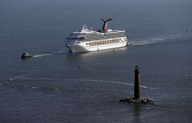 The disabled Carnival Lines cruise ship Triumph is towed to harbor off Mobile Bay, Ala., Thursday, Feb. 14, 2013. The ship with more than 4,200 passengers and crew members has been idled for nearly a week in the Gulf of Mexico following an engine room fire. (AP Photo/Gerald Herbert) Photo: Gerald Herbert, Associated Press