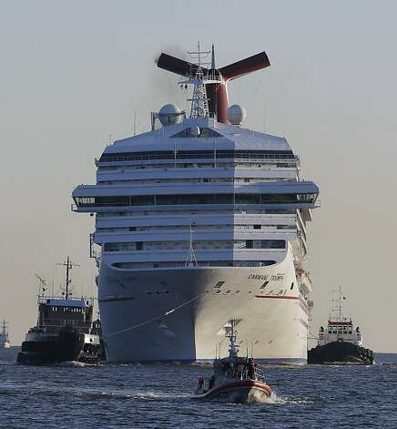 The cruise ship Carnival Triumph is towed into Mobile Bay near Dauphin Island, Ala., Thursday, Feb. 14, 2013. The ship with more than 4,200 passengers and crew members has been idled for nearly a week in the Gulf of Mexico following an engine room fire. (AP Photo/Dave Martin) Photo: Dave Martin, Associated Press
