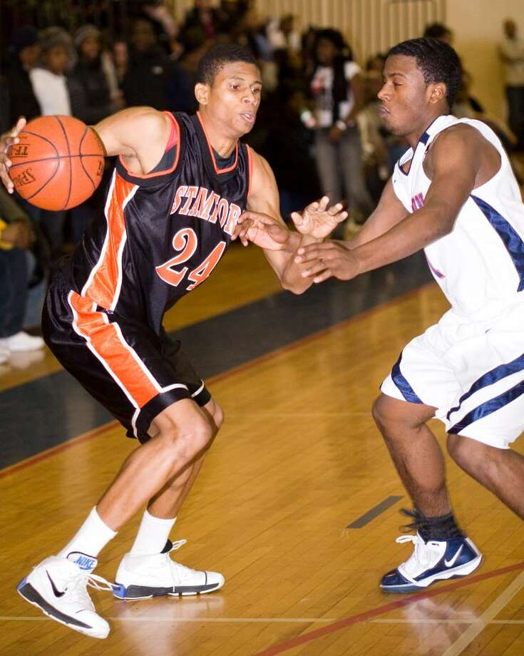 Stamford High School's #24 Marc Guirand, left, dribbles toward the basket as he's guarded by Brien McMahon High School's #1 Andre McCrae, right, during a boys basketball game in Norwalk. Photo: Kerry Sherck / Stamford Advocate