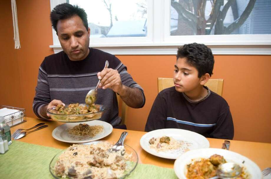 Hamid Kiani, left, and one of his sons, Fahad, 11, prepare to eat a traditional Pakistani dinner at the Kiani's home in Stamford, Conn. on Monday, Dec. 21, 2009. Photo: Chris Preovolos / Stamford Advocate