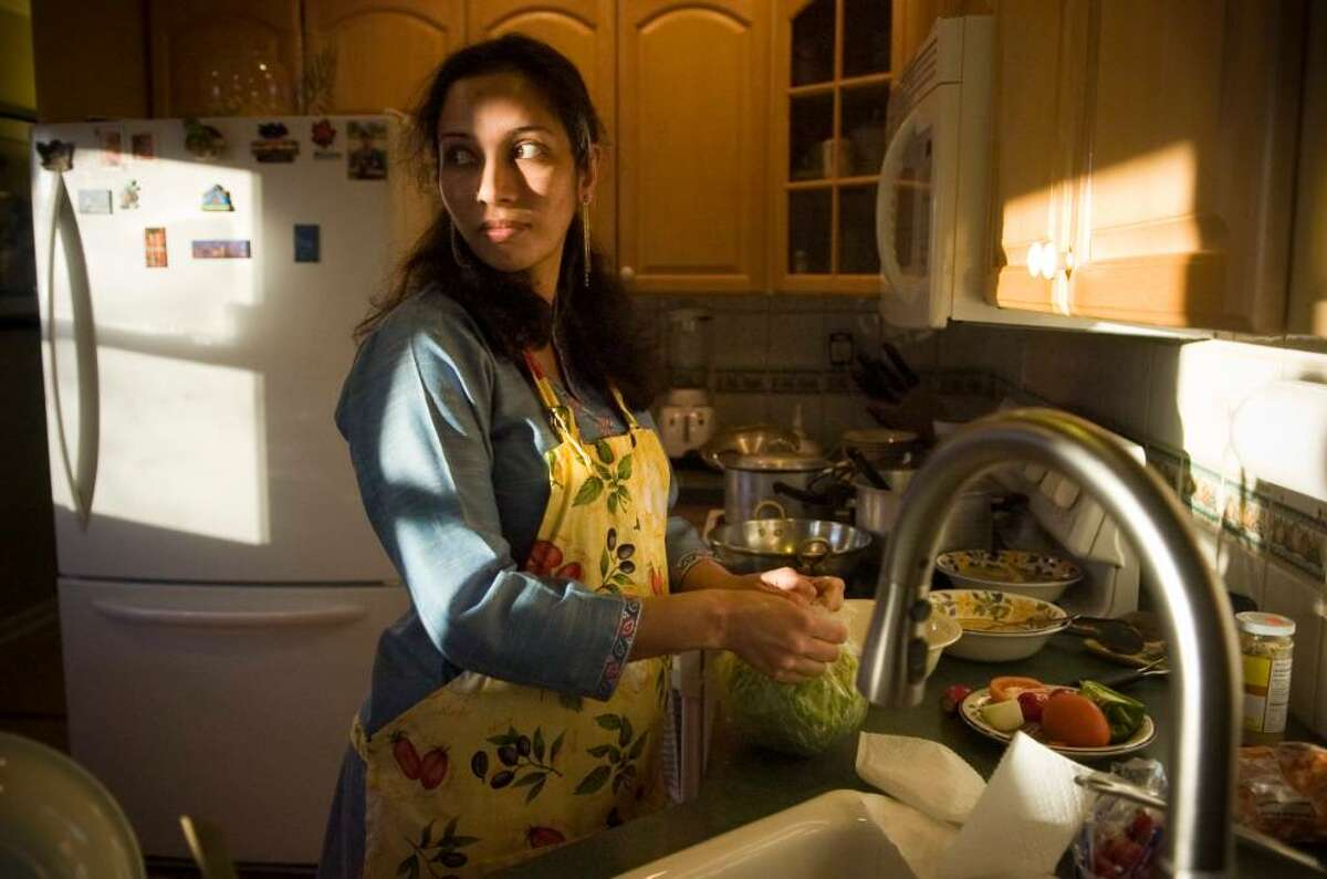 Amnah Kiani prepares a salad for a traditional Pakistani dinner at the Kiani's home in Stamford, Conn. on Monday, Dec. 21, 2009.