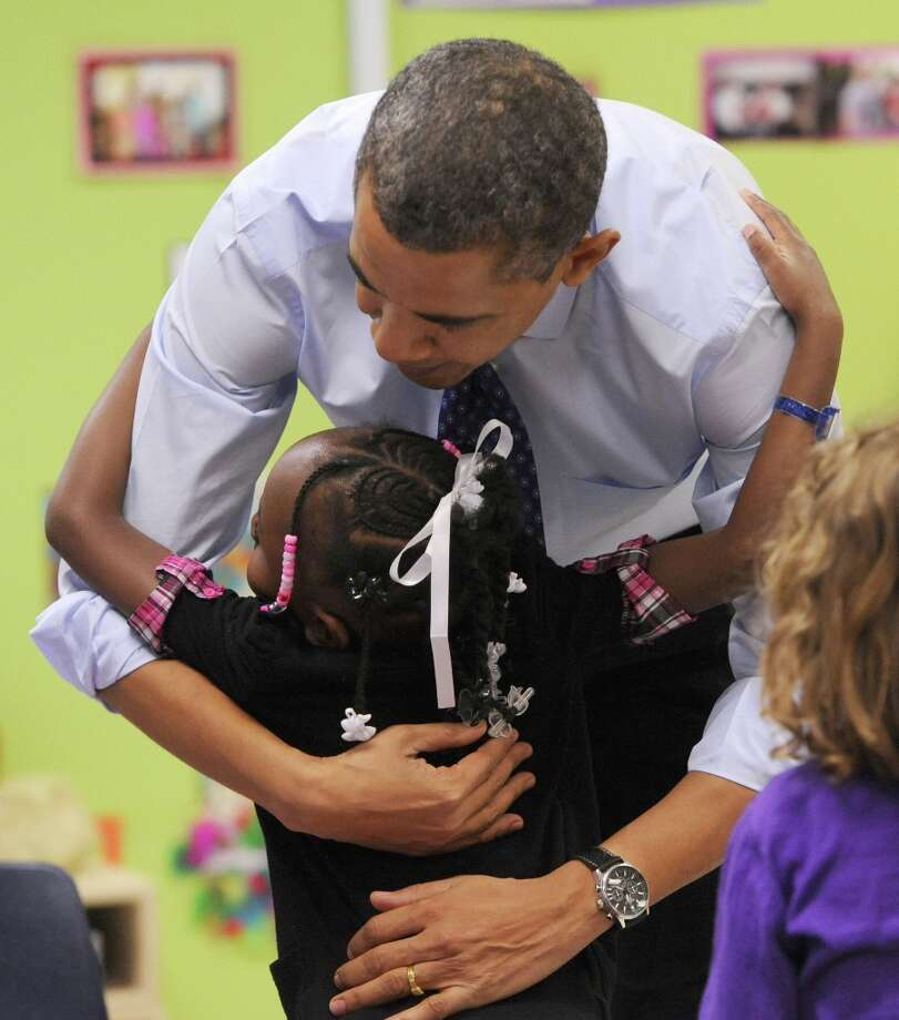United States President Barack Obama gets a hug from a child at College Heights Early Childhood Learning Center, in Decatur, Ga., on Thursday, Feb. 14, 2013. He visited the school to highlight their pre-kindergarten program. Photo: Johnny Crawford, Associated Press / Atlanta Journal-Constitution Poo