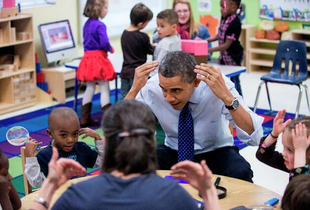 President Barack Obama plays a learning game while visiting children at College Heights Early Childhood Learning Center February 14, 2012 in Decatur, Ga. Photo: BRENDAN SMIALOWSKI, AFP/Getty Images / 2012 Brendan Smialowski