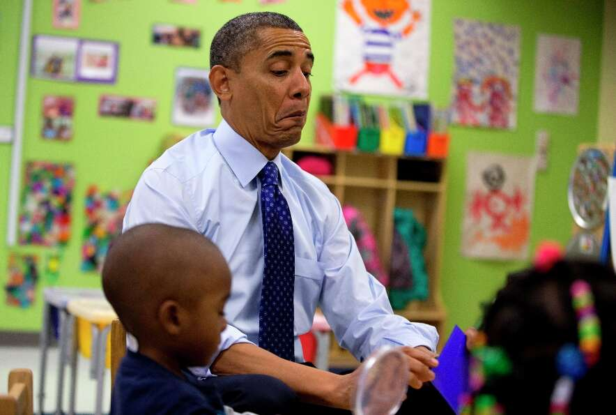 President Barack Obama reacts as he draws a card during a learning game during a visit to a pre-kind