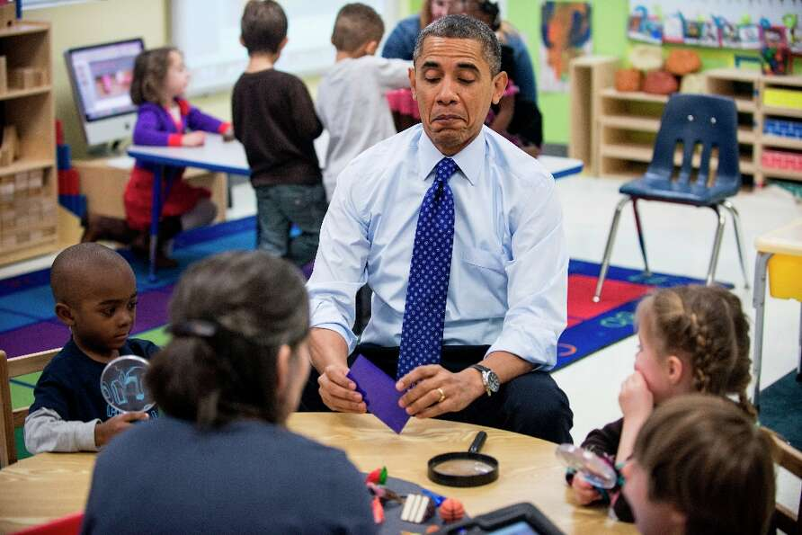 President Barack Obama plays a learning game while visiting children at College Heights Early Childh