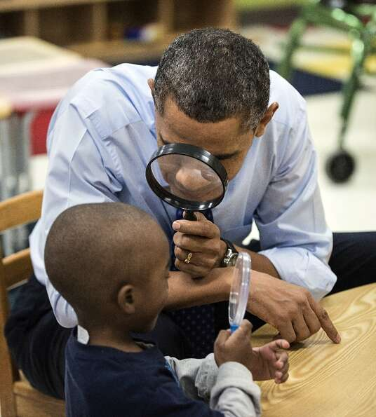 President Barack Obama looks at a boy with a magnifying glass while visiting children at College Hei