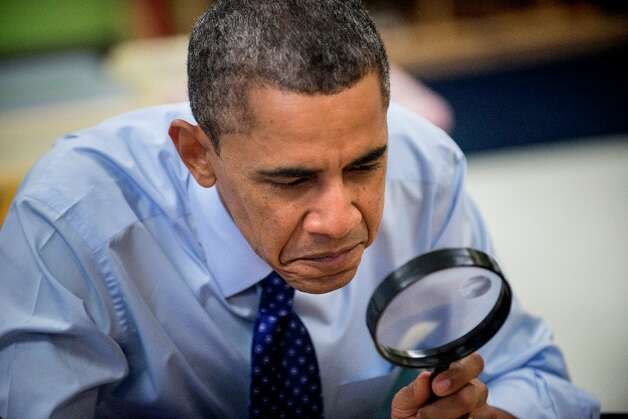 President Barack Obama uses a magnifying glass while he plays a learning game while visiting children at College Heights Early Childhood Learning Center February 14, 2012 in Decatur, Ga. Photo: BRENDAN SMIALOWSKI, AFP/Getty Images / 2012 Brendan Smialowski