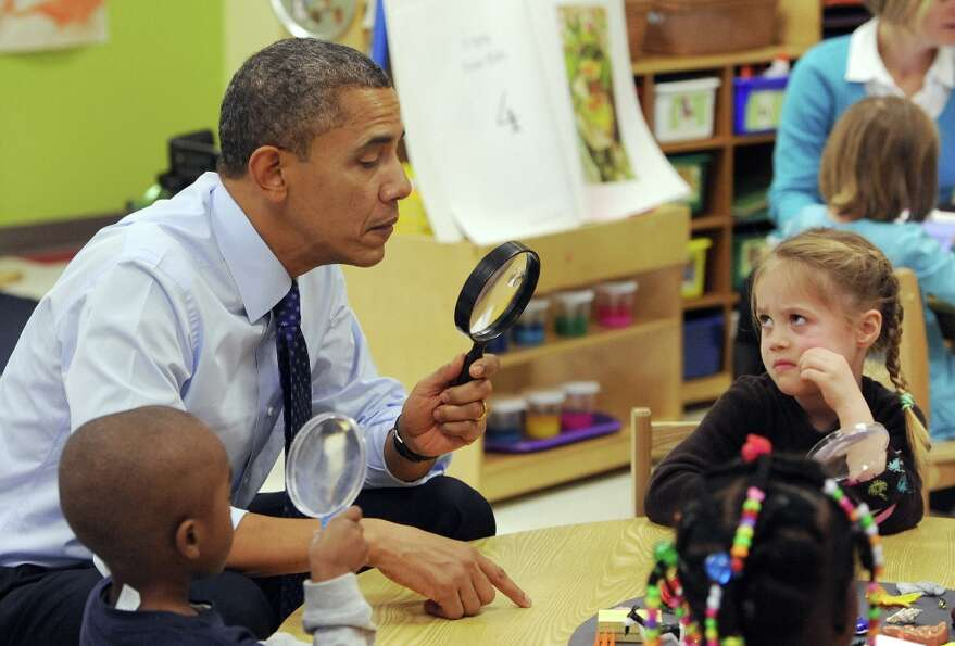 President Barack Obama looks through a spy glass as a little girl stares at him during a visit to Co