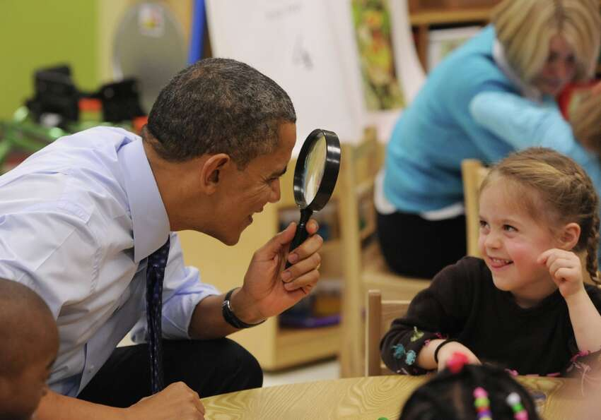 President Barack Obama uses a spy glass to play with a young girl during a visit to College Heights