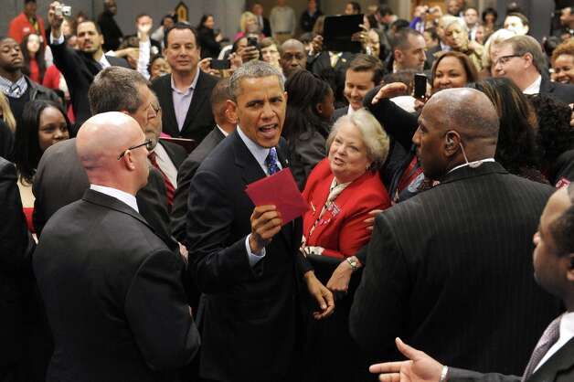 President Barack Obama hands an aide a Valentine card that he received from a young girl at the Decatur Recreation Center in Decatur, Ga. on Thursday, Feb. 14, 2013. Photo: Johnny Crawford, Associated Press / AJC
