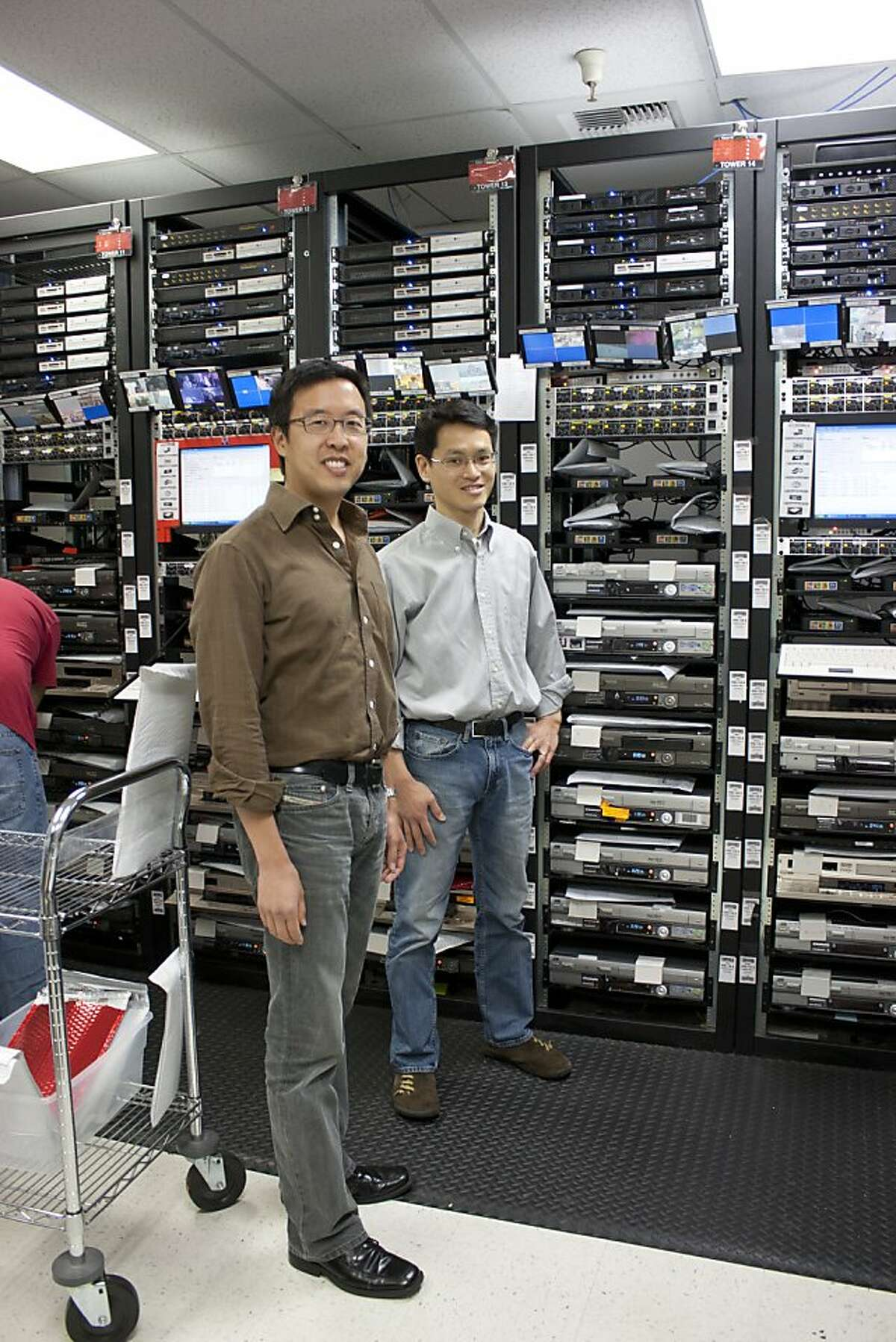 Michael Chang (CEO in brown shirt, left) and Andy Choi (CTO in light shirt, right) amidst towers of VCRs at the YesVideo headquarters in Santa Clara.