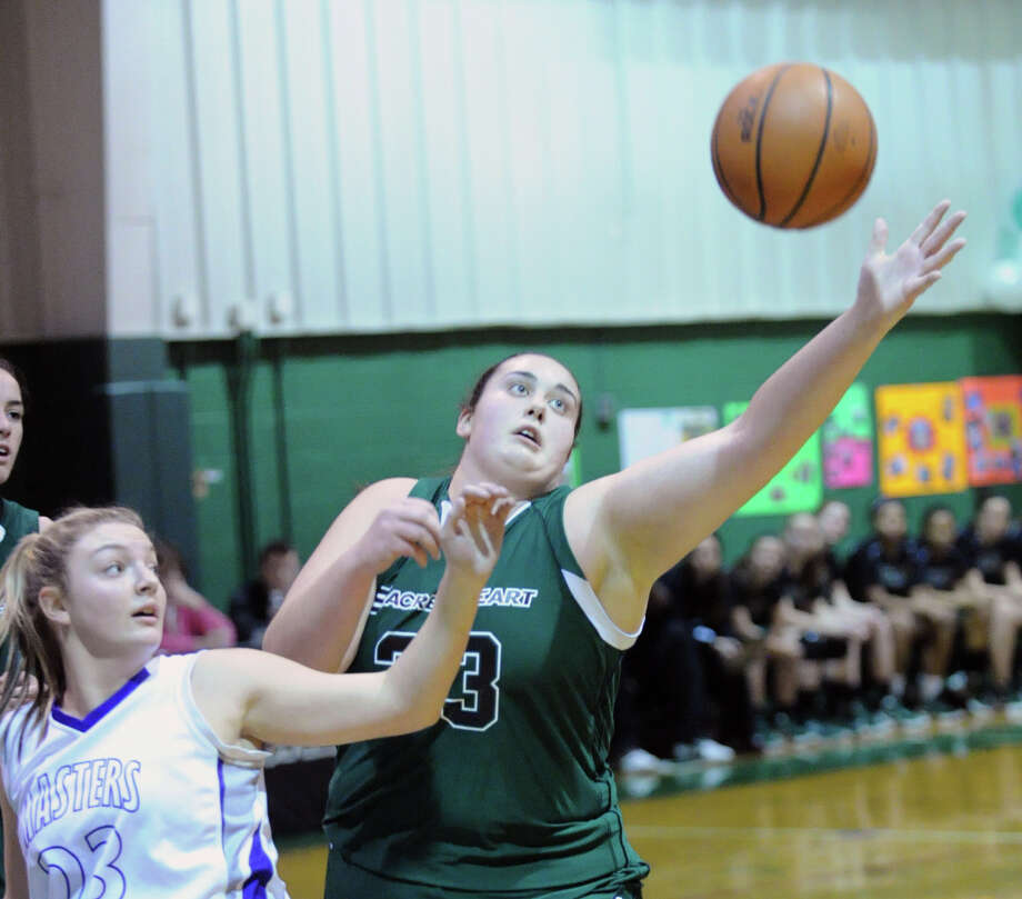 At right, Emily O'Sullivan # 33 of Convent goes for the ball along with Gianna Masini # 23 of Masters during the girls high school basketball game between Masters and Convent of the Sacred Heart at the Convent in Greenwich, Thursday, Feb. 14, 2013. Photo: Bob Luckey / Greenwich Time