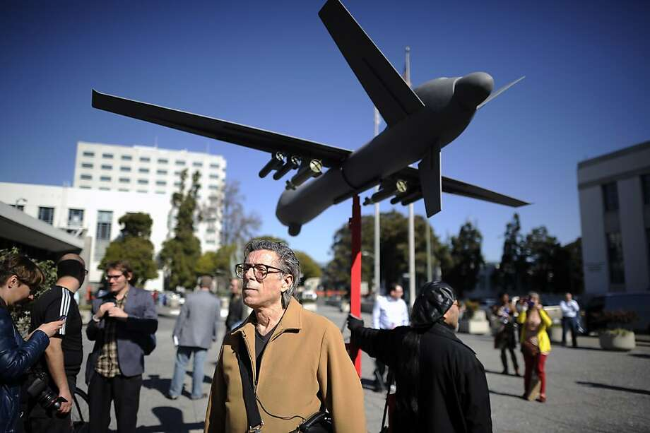 Curt Wechsler and other protesters rally beneath a mock-up of a drone equipped with missiles outside the Alameda County Administration Building in Oakland. Photo: Michael Short, Special To The Chronicle