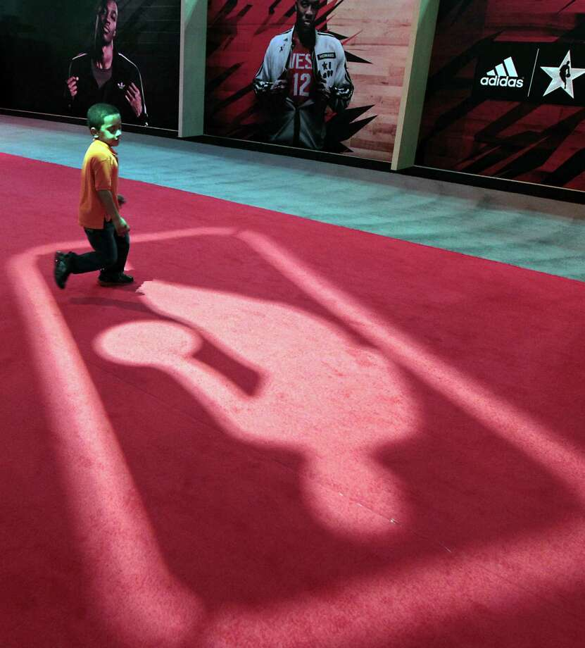 Six-year-old Miciah Simon chases a floor projection at the NBA All-Star Jam Session during NBA All-Star weekend at the George R. Brown Convention Center. Photo: James Nielsen, Chronicle / © Houston Chronicle 2013