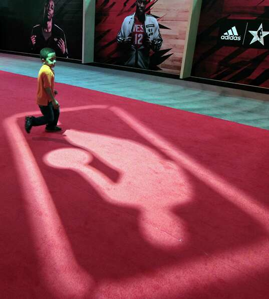 Six-year-old Miciah Simon chases a floor projection at the NBA All-Star Jam Session during NBA All-S