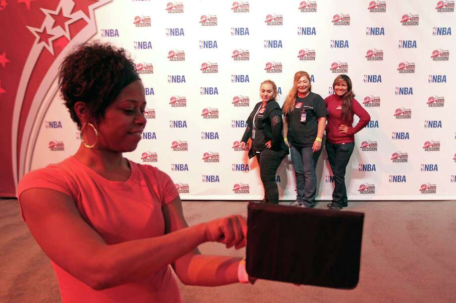 Carla Randolph takes a photograph of Christy Pena, Herminia Alba and Veronica Castillo at the NBA All-Star Jam Session. Photo: James Nielsen, Chronicle / © Houston Chronicle 2013