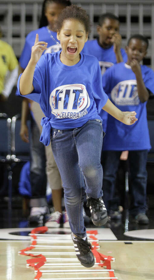 Chassidy Hill, 7, goes through a fitness drill during the NBA FIT All-Star Youth Celebration. Photo: Melissa Phillip, Houston Chronicle / © 2013 Houston Chronicle