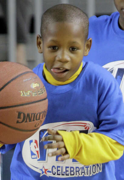 Anthony Thomas, 7, works on a ball handling drill during the NBA FIT All-Star Youth Celebration.
