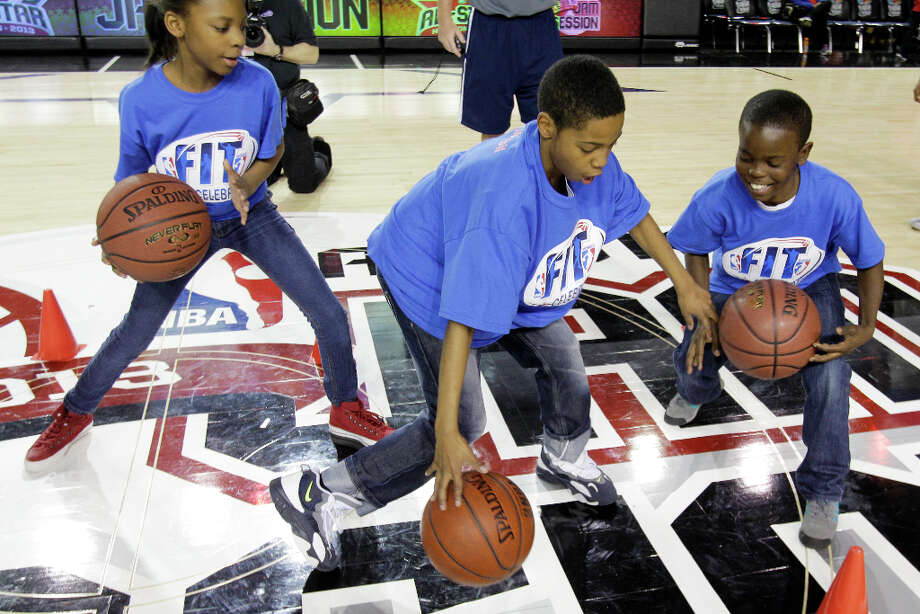 Cherish Adams, 10, left, Jadon Phillips, 10, center, and Jakendrick Terrell, 10, right, work on a ball handling drill during the NBA FIT All-Star Youth Celebration. Photo: Melissa Phillip, Houston Chronicle / © 2013 Houston Chronicle