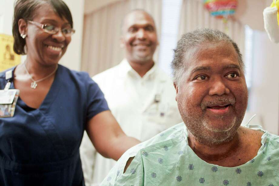 Small victories - like sitting up unassisted for about 30 seconds - bring a smile to the face of Dwight Jones, 60, as the former basketball star works to get stronger with help from physical therapist technicians Tonya Basey and Phillip Matthews. Photo: Johnny Hanson, Staff / © 2013  Houston Chronicle