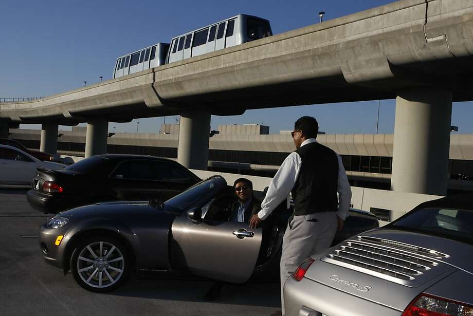 Ric Macapinlac (in car) and Steven King park a car at San Francisco International Airport. The company will rent cars to arriving passengers in exchange for free parking and a gas gift card for the vehicle's owner. Photo: Liz Hafalia, The Chronicle