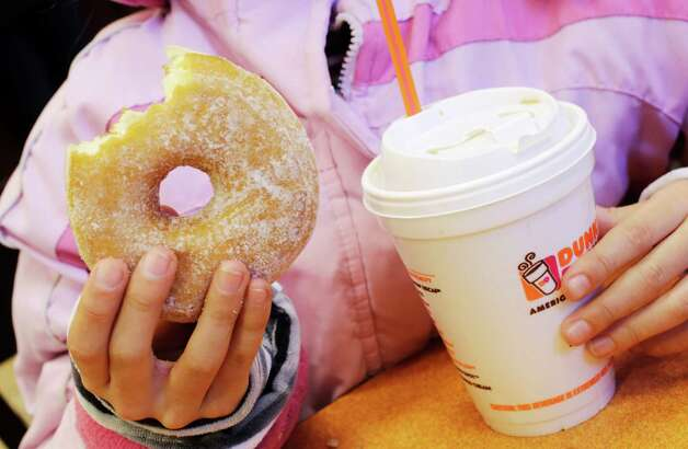 A girl has a doughnut and a beverage, served in a foam cup, at a Dunkin' Donuts in New York Thursday, Feb. 14, 2013. New York Mayor Michael Bloomberg, who has taken on smoking, sugary drinks and salt, talked about banning food packaging made from polystyrene foam from stores and restaurants in his annual State of the City address on Thursday. (AP Photo/Mark Lennihan) Photo: Mark Lennihan