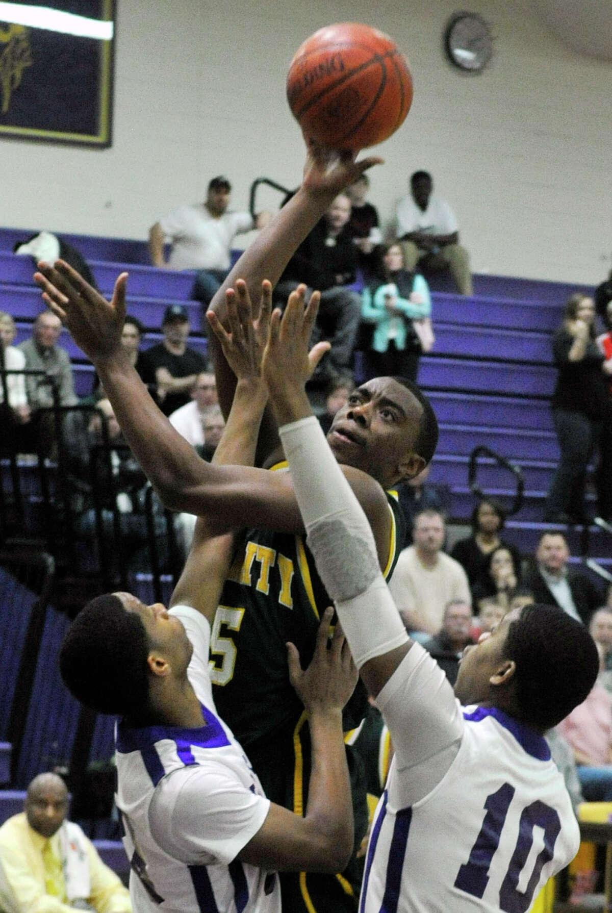 Trinity Catholic's Brandon Wheeler shoots over Westhill's Ariel DelaCruz, left, and Yveson Cassamajor during their City Championship game at Westhill High School in Stamford on Thursday, Feb. 14, 2013. Trinity Catholic won, 62-46.