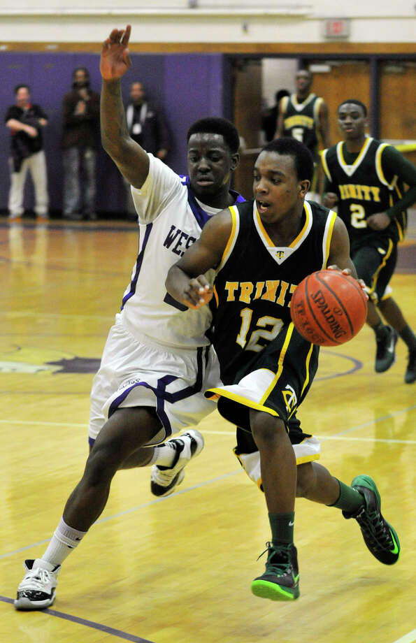 Trinity Catholic's Tyrell St. John drives to the basket while under pressure from Westhill's Terrell Middleton during their City Championship game at Westhill High School in Stamford on Thursday, Feb. 14, 2013. Trinity Catholic won, 62-46. Photo: Jason Rearick / The News-Times