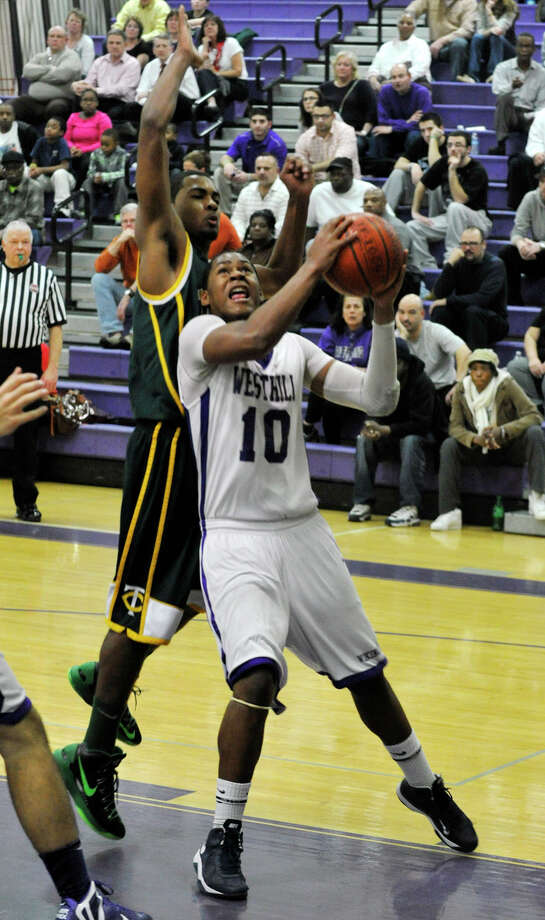 Westhill's Yvesoon Cassamajor drives to the basket while under pressure from Trinity Catholic's Neno Merritt during their City Championship game at Westhill High School in Stamford on Thursday, Feb. 14, 2013. Trinity Catholic won, 62-46. Photo: Jason Rearick / The News-Times