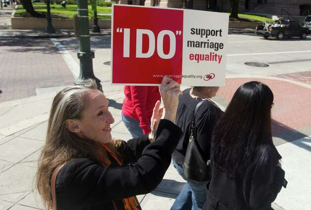 Kristen Klein-Cechettini and close to a dozen same-sex couples march from the Harris County Clerk's office to Houston City Hall after being denied a marriage license on Thursday, Feb. 14, 2013, in Houston. Photo: J. Patric Schneider, For The Chronicle / © 2013 Houston Chronicle