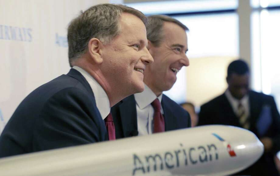 U.S. Airways CEO Doug Parker, left, and American Airlines CEO Tom Horton laugh during a news conference at DFW International Airport Thursday, Feb. 14, 2013, in Grapevine, Texas. The two airlines will merge forming the world's largest airlines.  (AP Photo/LM Otero) Photo: LM Otero, STF / AP