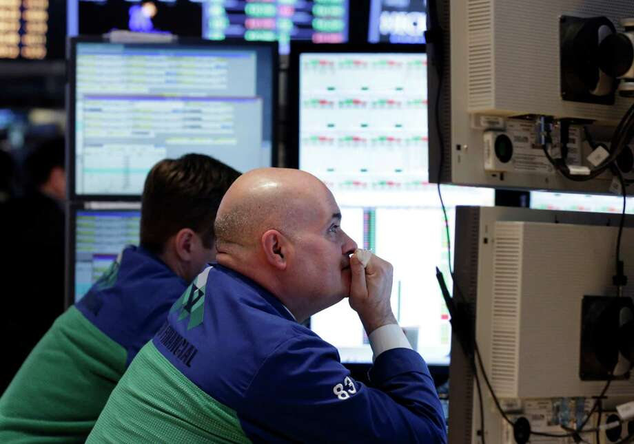 Specialist Anthony Confusione, right, works at his post on the floor of the New York Stock Exchange Thursday, Feb. 14, 2013. Renewed worries about Europe overshadowed an encouraging U.S. jobs report, and stocks flipped between slight gains and losses on Thursday. (AP Photo/Richard Drew) Photo: Richard Drew