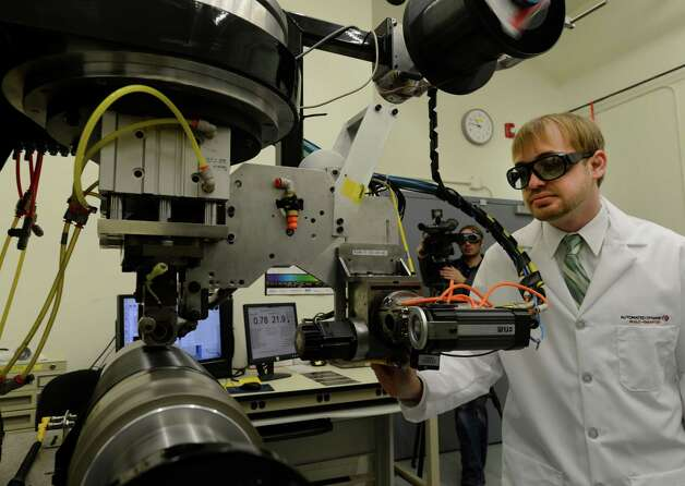 Project Engineer Zachary August runs a laser aided production machine which produces high-end composite items at Auto Dynamics was demonstrated after the announcement of a grant of $400,000 from NYSERDA Feb. 14, 2013 in Schenectady, N.Y.    Automated Dynamics and two other local companies were lauded for new energy saving technologies used at their companies.  ThermoAura of Troy and Evocative of Green Island were each given grants of $393,000 and $350,000 respectively.  (Skip Dickstein/Times Union) Photo: SKIP DICKSTEIN / 00021180A