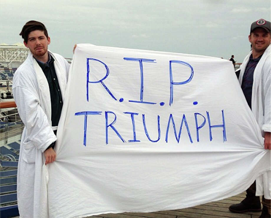 An Instagram photo provided by a passenger of the Carnival Cruise Ship Triumph identifying himself as Clarkaj shows passengers with a handmade banner at the deck of the ship on Wednesday.  Photo: CLARKAJ, AFP/Getty Images / AFP