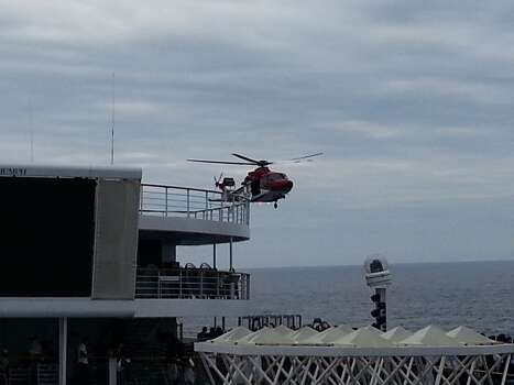 A photo from passenger Natalie Magoulas shows a helicopter flying near the ship. A Coast Guard helicopter ferried a generator and other equipment to the ship on Wednesday, the Chicago Tribune reports.