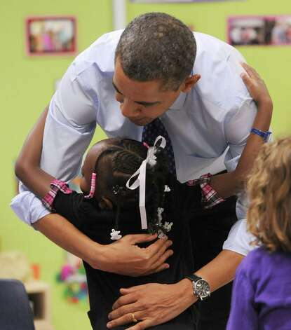 United States President Barack Obama gets a hug from a child at College Heights Early Childhood Learning Center, in Decatur, Ga., on Thursday, Feb. 14, 2013. He visited the school to highlight their pre-kindergarten program. He is proposing a nationwide initiative for children in pre-kindergarten.  (AP Photo/Atlanta Journal-Constitution, Johnny Crawford, Pool) Photo: Johnny Crawford