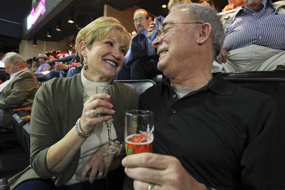 Diane and Ed Snoble enjoy glasses of champagne while watching rodeo action as the rodeo hosts the Dust & Bubbles event for Valentine's Day with champagne and food in a special suite. Photo: Tom Reel / San Antonio Express-News