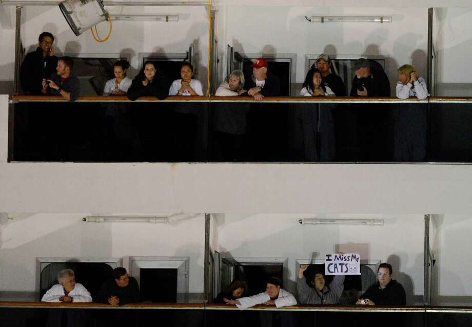 People watch from their balconies aboard the Carnival Triumph after it was towed to the cruise terminal in Mobile, Ala., Thursday, Feb. 14, 2013. The ship with more than 4,200 passengers and crew members has been idled for nearly a week in the Gulf of Mexico following an engine room fire. (AP Photo/John David Mercer) Photo: John David Mercer, Associated Press / FR20630 AP