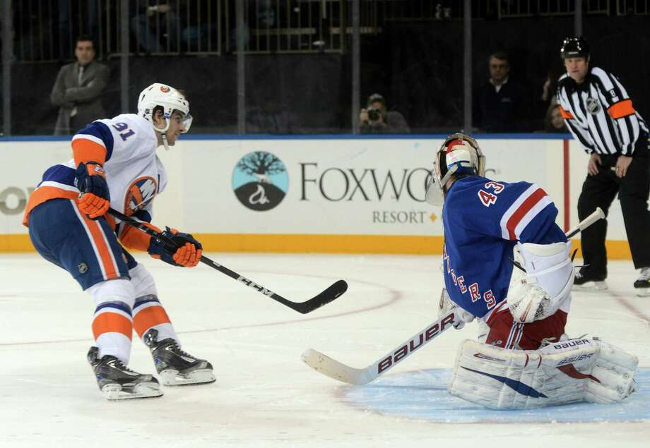 New York Islanders' John Tavares, left, scores past New York Rangers goalie Martin Biron in the shootout of the NHL hockey game at Madison Square Garden in New York, Thursday, Feb. 14, 2013. The Islanders won 4-3. (AP Photo/Henny Ray Abrams) Photo: Henny Ray Abrams