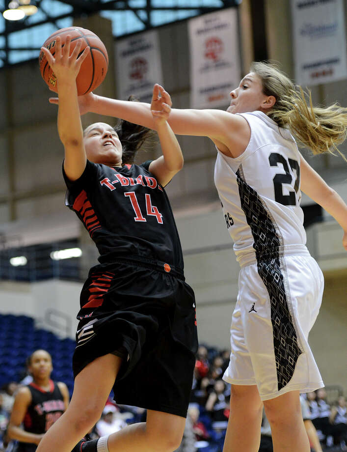 Wagner's Amber Ramirez (14) is fouled by Clark's Kristen Lye (22) as she puts up a shot during a 5A girls second round playoff basketball game between the Wagner Thunderbirds and the Clark Cougars at the UTSA Convocation Center, Thursday, February 14, 2013. 