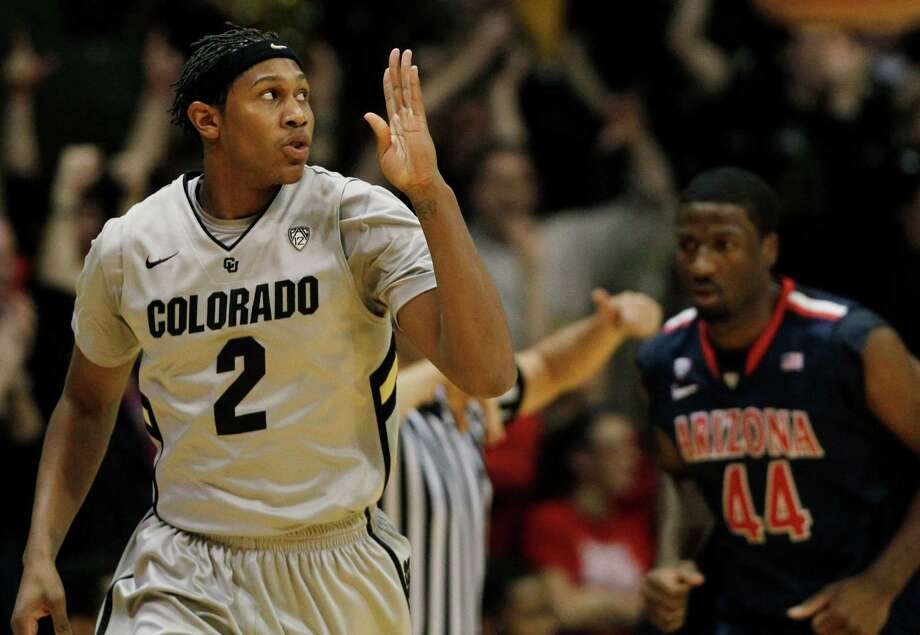Colorado forward Xavier Johnson, left, signals his 3-pointer that helped the Buffaloes open a first-half lead they never surrendered against No. 9 Arizona. Photo: David Zalubowski, STF / AP